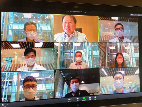 SK Group Chairman Chey Tae-won, center in the first row, speaks with the researchers at SK Bioscience in a teleconference on Monday. [SK GROUP]