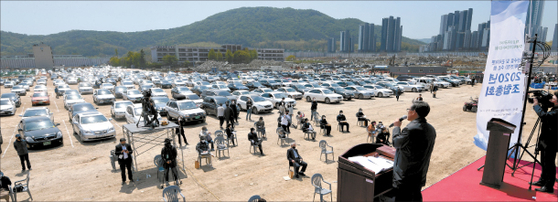 The owners of apartments at Gaepo 1 Danji gathered at Gaewon Elementary School within the apartment complex to discuss the reconstruction project on Tuesday in Gangnam, southern Seoul. While some sat in chairs that were set apart to keep social distancing, some of the apartment owners attending the meeting remained seated in their cars to avoid the coronavirus. [YONHAP]