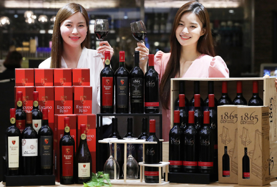Models pose with wine at Lotte Department Store's branch in central Seoul on Tuesday. The retailer said throughout May it is holding a sale on Chilean wines 1865 and Escudo Rojo. [YONHAP]