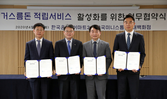 From left to right are Emart24 CEO Kim Song-yong, Bank of Korea Deputy Governor Yoon Myun-shik, Ministop Korea President Shim Kwan-sub and Hyundai Department Store Executive Vice President Jung Jee-young at the central bank's headquarters in central Seoul on Tuesday. [EMART24]