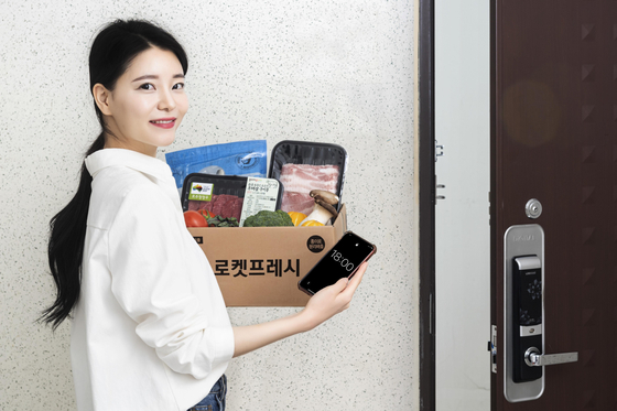 A model holds up groceries delivered through Coupang's same-day delivery service. [COUPANG]