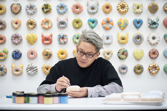 Jae Yong Kim paints a small doughnut in front of a wall covered in his works. His first solo exhibition since he returned to Korea in 2015 is being held at the Hakgojae Gallery in central Seoul until May 31. [HAKGOJAE GALLERY]