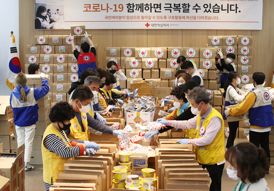 Volunteers of the Korean Red Cross package snacks for health care workers treating Covid-19 patients Tuesday at the group's office in Suwon, Gyeonggi. [YONHAP]