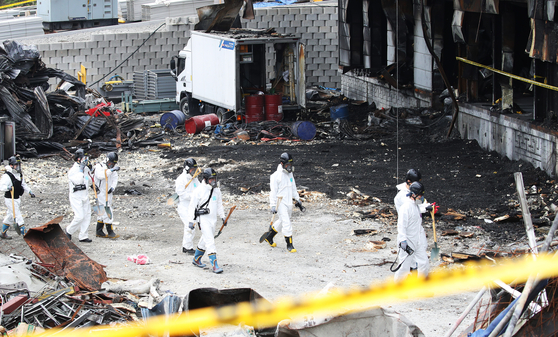 Police forensic investigators on Sunday search for missing remains of victims killed by a warehouse fire in Icheon, Gyeonggi, last week. [YONHAP]