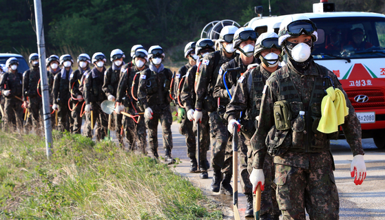 Soldiers walk towards a mountain in Goseong County, Gangwon, on Saturday morning to help extinguish a wildfire that began the previous night. [NEWS1]