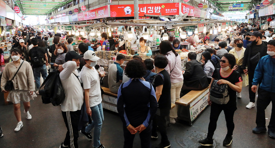 People crowd Gwangjang Market in Jongno District, central Seoul, Sunday, after the Korean central government announced that the current social distancing campaign will end as planned on Tuesday and be replaced with a campaign of looser restrictions. [NEWS1]