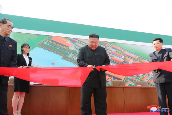 North Korean leader Kim Jong-un, emerging after 20 days in seclusion, cuts a ribbon at a ceremony on Friday to open a new fertilizer factory in Sunchon, South Pyongan Province. [YONHAP]