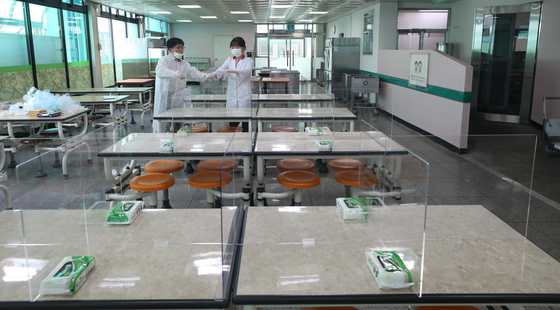 Teachers set up dividers on lunch tables at a high school in western Seoul on Monday, as they prepare for the first day of classes next week. [NEWS1]