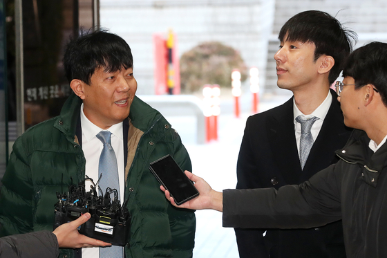 Socar CEO Lee Jae-woong, left, and VCNC CEO Park Jae-uk, answer questions from reporters at their first hearing on charges of violating the Passenger Transport Service Act at the Seoul Central District Court in Seocho District, southern Seoul, last December. [JANG JIN-YOUNG]
