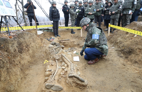 Former Prime Minister Lee Nak-yon kneels in front of the remains of a fallen soldier that were excavated at Arrowhead Ridge in the demilitarized zone (DMZ) last November. [YONHAP]