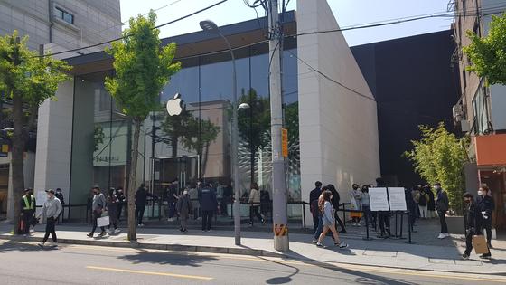 At Korea's only Apple store, in Garosu-gil, Gangnam in southern Seoul, customers line up to enter the establishment Thursday. [KANG JAE-EUN]