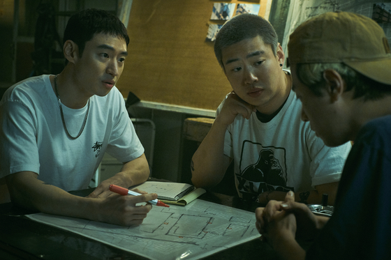 "In a scene from 'Time to Hunt."" Jun-seok (played by Lee Je-hoon), far left, and his friends discuss how to rob a gambling place. [NETFLIX]"