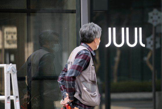 A man helps shut down a Juul Labs store in Gwangwhamun in central Seoul in March. The U.S.-based e-cigarette maker on Wednesday said it is halting operations in Korea. [YONHAP]