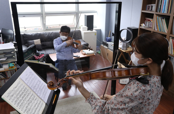 A music professor at Seoul National University instructs his student in viola while separated by a transparent divider set up to abide by social distancing guidelines. [YONHAP]