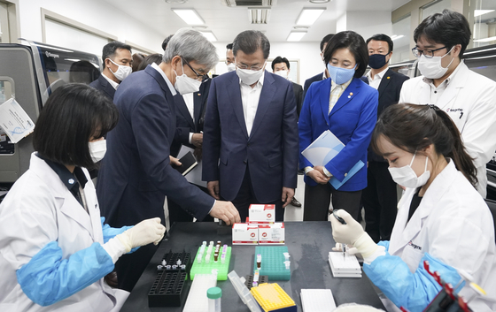 President Moon Jae-in, center, examines a Seegene research facility during his visit to the company's headquarters in Seoul in March. Moon visited the local diagnostic kit manufacturing company following his phone conversation with U.S. President Donald Trump hours earlier. [YONHAP]