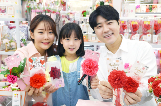 Models show carnation brooches at the Family Month Exhibition section at Daiso's Coex branch in Gangnam District, southern Seoul on Thursday for the upcoming Parents' Day. [ASUNG DAISO]