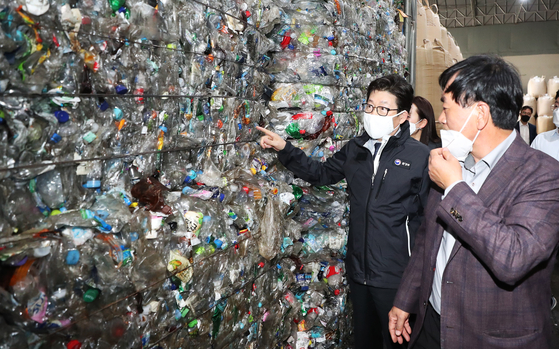 Environment Minister Cho Myung-rae inspects a PET recycling company in Hwaseong, Gyeonggi, on Thursday. The Ministry of Environment is buying up 10,000 tons of PET materials together with the Korea Environment Corporation starting July 7. Amid the coronavirus, PET has accumulated due to the weak economy, falling oil prices and a sharp drop in exports. [YONHAP]