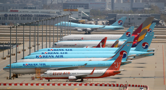 Korean Air Lines and Asiana Airlines carriers stand idle at Incheon International Airport last month. [YONHAP]