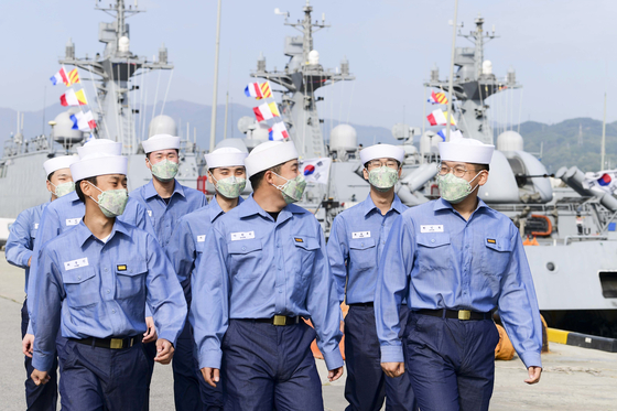 Sailors, wearing face masks, disembark from their battle ship on Wednesday after the central government officially ended social distancing campaign. [YONHAP]