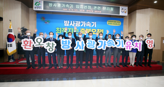 Public officials from Cheongju in North Chungcheong welcome the Science Ministry's decision to designate the city to host a new synchrotron radiation accelerator on Friday at the North Chungcheong Provincial Office. [YONHAP]