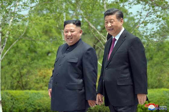 Chinese President Xi Jinping, right, and North Korean leader Kim Jong-un take a walk at the Kumsusan State Guesthouse in Pyongyang on June 21, 2019, in this photo released by the North's state-run Korean Central News Agency. [YONHAP]