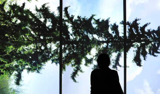 """A guest at the MMCA Seoul's new exhibition 'Axis of Horizon"""" looks at Eija-Liisa Ahtila's 'Horizontal-Vaakasuora"""" (2011), which depicts the difficulty in capturing nature -- and any other subject -- in its truest form, and rethinking the relationship between people and nature. [YONHAP]"""