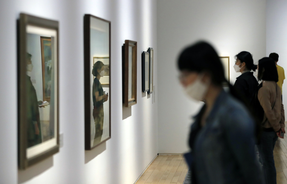 """Visitors look at works on display at MMCA Seoul's permanent exhibition 'MMCA Collection Highlights 2020+"""" on Thursday in central Seoul while wearing masks and standing away from each other in an effort to abide by social distancing guidelines. [YONHAP]"""