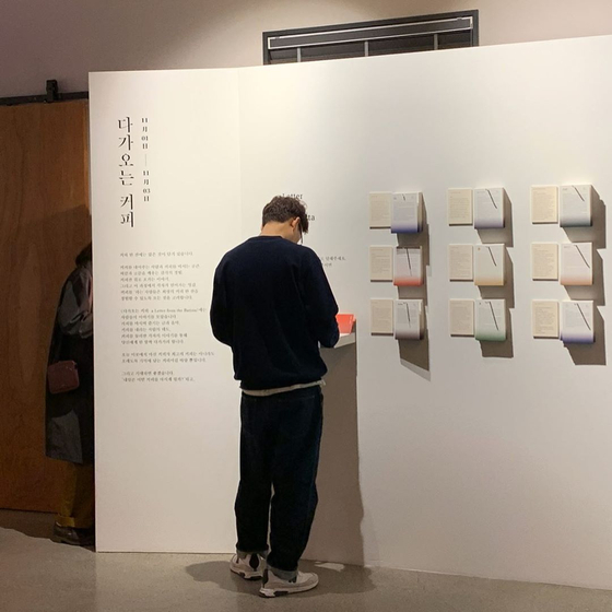 """A visitor looks around an exhibition titled 'A Letter from the Barista"""" held at Cociety last November. The exhibit, which a group of baristas took part in, was organized to provide a better understanding of the local coffee industry. [COCIETY]"""