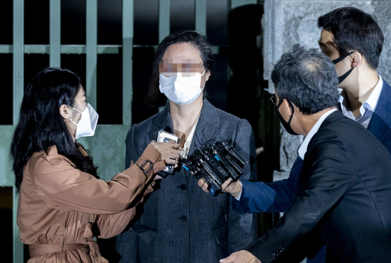 Chung Kyung-sim, second from left, the wife of former Justice Minister Cho Kuk, is questioned by reporters as she is released on bail Sunday morning. [YONHAP]
