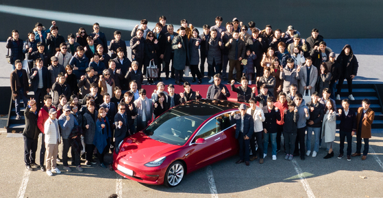 Tesla Model 3 owners pose at an event at Seoul Grand Park in Gwacheon, Gyeonggi, last year, celebrating the arrival of the electric vehicles. [YONHAP]
