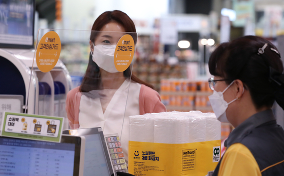 A cashier checks out goods behind a protective plastic shield to minimize the risk of coronavirus infection on Monday at Emart's Seongsu branch in eastern Seoul. Emart announced it would to install plastic shields in 155 different branches nationwide after introducing them in Daegu and North Gyeongsang branches last month. [YONHAP]