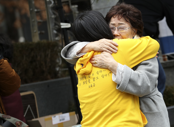 "Lee Yong-soo, a former ""comfort woman,"" right, hugged Yoon Mee-hyung, former head of the Korean Council, during the Wednesday demonstration in front of the Japanese Embassy on Jan. 8, 2020. Their relationship of 30 years recently fell apart after Lee's press conference criticizing Yoon's integrity. [YONHAP]"