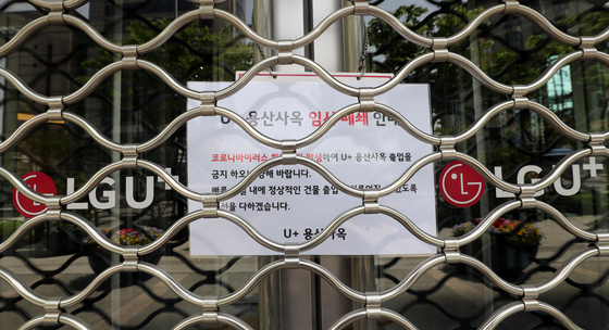A note at the building of mobile carrier LG U+'s headquarters in Yongsan District, central Seoul, informs of a temporary shutdown on Monday. [YONHAP]