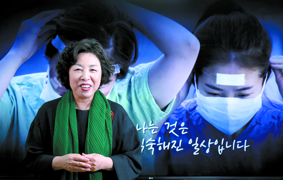 Shin Kyung-rim poses in front of a video that showcases the role of nurses in the coronavirus outbreak. [KIM KYUNG-BIN]