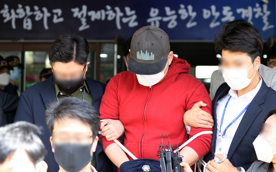 "The suspect allegedly behind an online pornography ring known by the internet alias ""God God"" leaves a police precinct in Andong, North Gyeongsang, to attend a court hearing for his arrest on Tuesday. [YONHAP]"