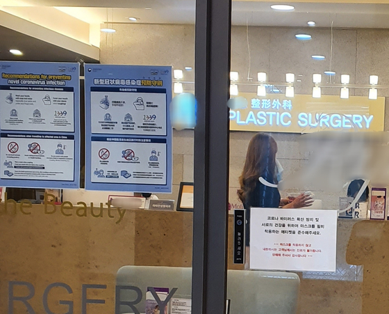 A sign on the door says not to enter without a mask at a plastic surgery clinic in Gangnam District, southern Seoul. [PYUN GWANG-HYUN]