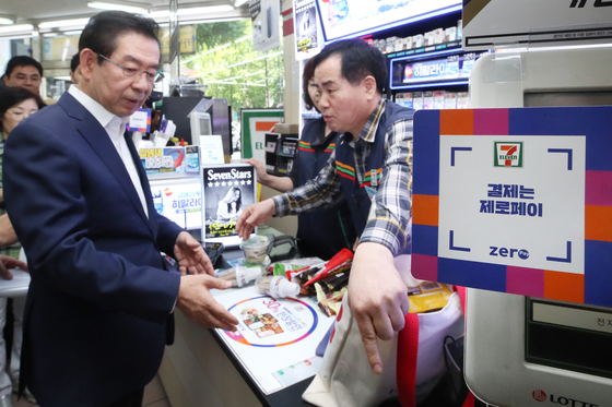 Seoul Mayor Park Won-soon, left, buys ice cream at a convenience store in Jung District, central Seoul, last September using Zero Pay. [YONHAP]
