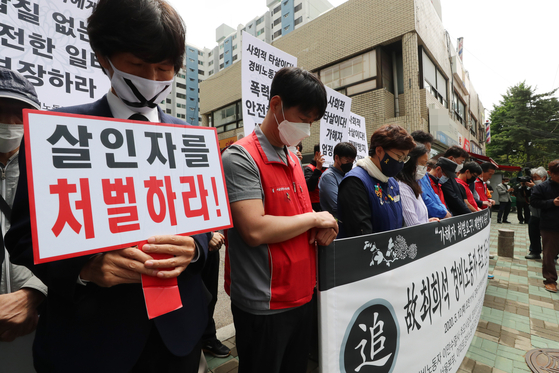 Civic group members hold a vigil Tuesday to mourn a security guard who took his own life after being subject to alleged physical and verbal abuse by an apartment resident. [YONHAP]