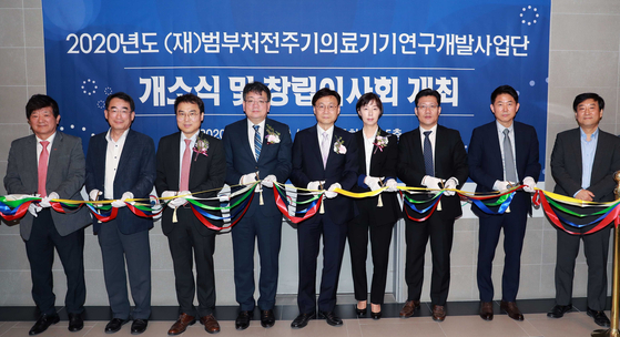 Government officials including Choi Nam-ho, director-general of manufacturing at the Ministry of Trade, Industry and Energy, fourth from left, cuts a ribbon at a ceremony launching a joint government team to promote and support Korea's biopharmaceutical and medical industries in Seoul on Wednesday. [YONHAP]