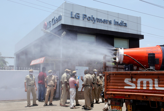 Municipal workers decontaminate the area outside of the LG Polymers plant following a gas leak at the plant in Visakhapatnam, India, on May 8. [REUTERS]