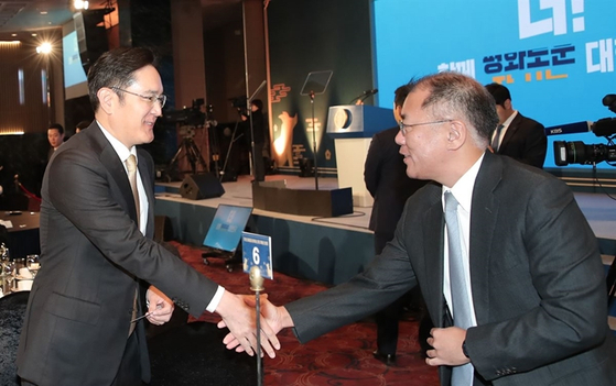 SamsungElectronics Vice Chairman Lee Jae-yong, left, and Hyundai Motor Executive ViceChairman Euisun Chung shake hands at an event at the Korea Federation of SMEs in Yeouido, western Seoul.