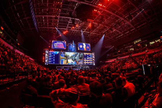 An e-sports stadium is filled with audiences watching an e-sports match