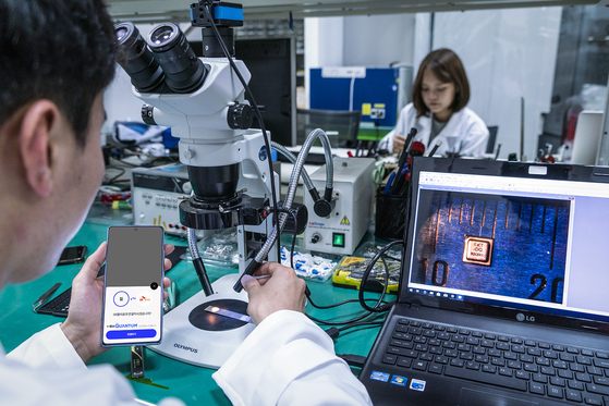 Researchers from SK Telecom affiliate IDQuantique test a quantumrandom number generator chipset to be installed in the Galaxy A Quantum at the telecom company's office in Bundang, Gyeonggi. [SK TELECOM]