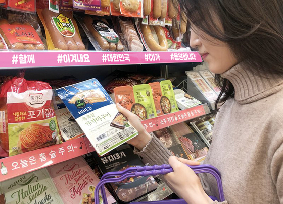 A customer is looking at a ready-to-eat meal at a CU convenience store. [BGF RETAIL]