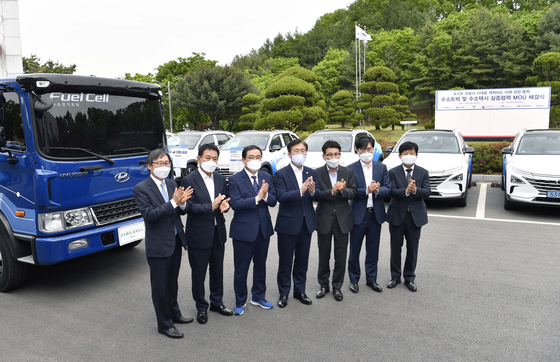 Trade Minister Sung Yun-mo, far left, and Hyundai Motor Group President Kong Young-woon, second from right, pose next to the fuel-cell truck that will be sent to the city of Changwon, South Gyeongsang, at the Korea Automotive Technology Institute in Cheonan, South Chungcheong, on Thursday. [YONHAP]
