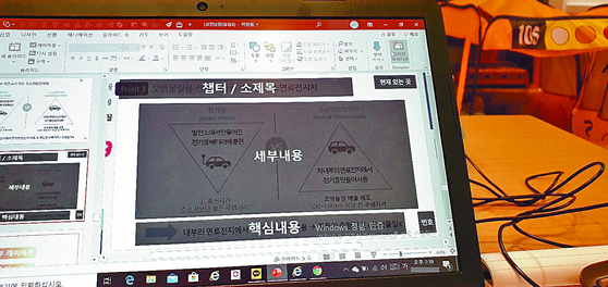 A office worker's computer displays a lecture on PowerPoint skills. [JOONGANG ILBO]