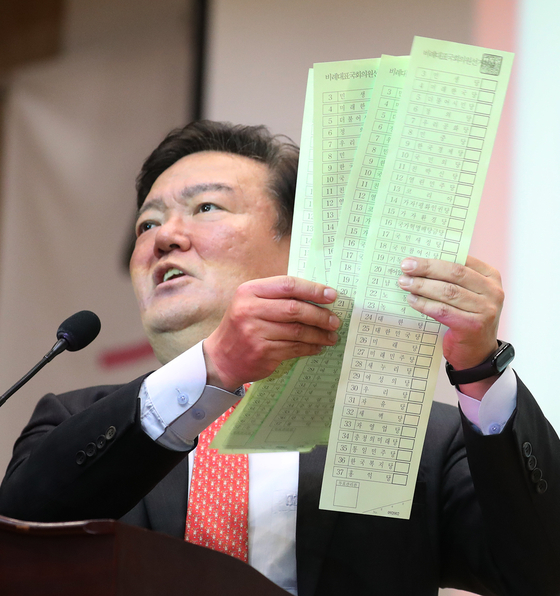 Rep. Min Kyung-wook shows six unmarked ballots during a press conference on Monday, calling them material evidence of vote rigging.  [YONHAP]