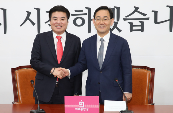 Future Korea Party Chairman Won Yoo-chul, left, and Rep. Joo Ho-young, floor leader and acting head of the United Future Party, shook hands before their joint conference on a merger agreement on Thursday.  [YONHAP]