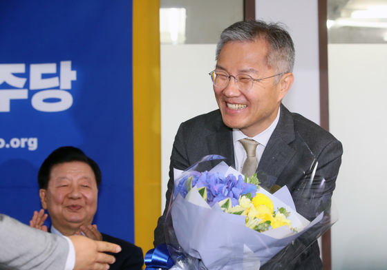 Lawmaker-elect Choe Kang-wook received a bouquet on Tuesday after he was elected the chairman of the Open Minjoo Party.  [YONHAP]