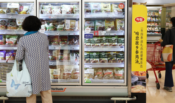 A customer peruses ready-to-eat meals in the refrigerated foods section at a discount store in Seoul. [YONHAP]